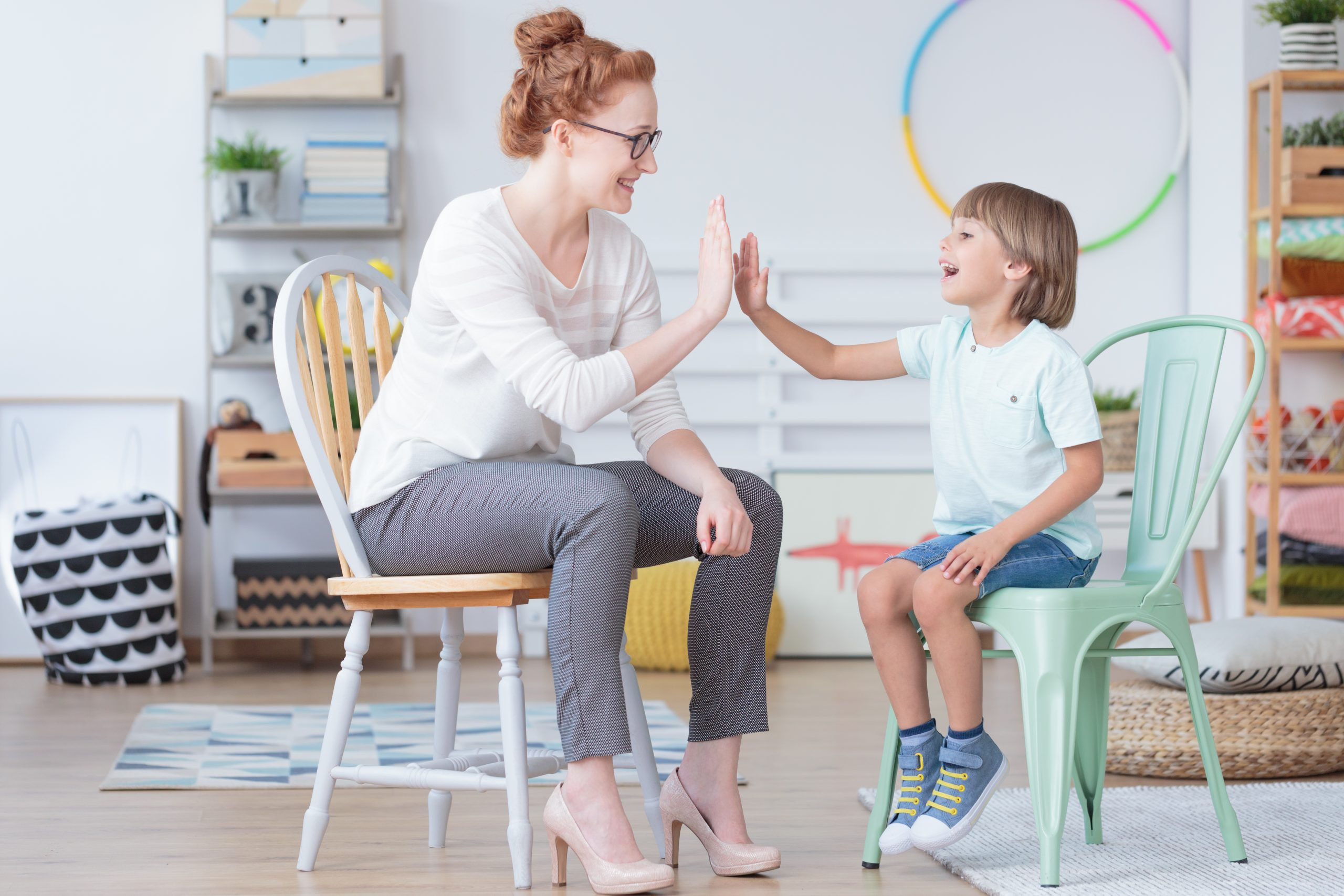 therapist giving child with autism high five during ABA therapy session