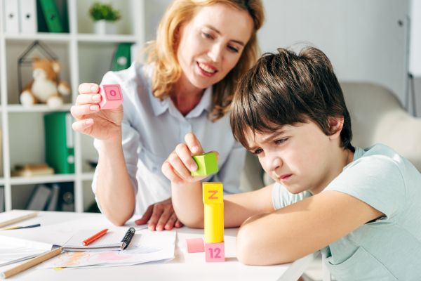 child with autism engaging in play therapy with teacher